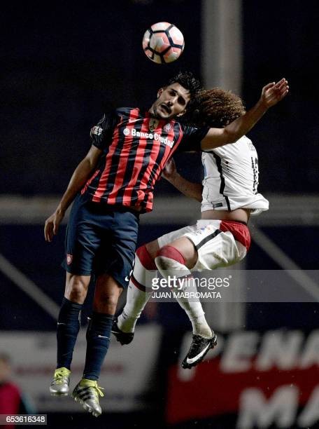 Argentina's San Lorenzo forward Nicolas Blandi vies for the ball with Brazil's Atletico Paranaense midfielder Felipe Gedoz during their Copa...