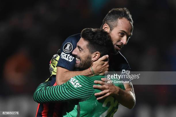 Argentina's San Lorenzo goalkeeper Jose Antonio Devecchi celebrates with teammate midfielder Fernando Daniel Belluschi after defeating Ecuador's...