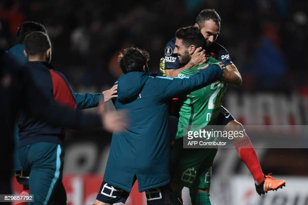 Argentina's San Lorenzo goalkeeper Nicolas Gaston Navarro celebrates with teammate midfielder Fernando Daniel Belluschi after defeating Ecuador's...