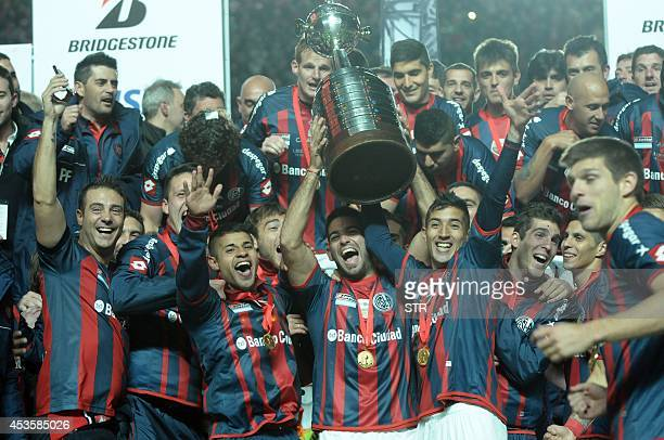 Argentina's San Lorenzo players hold up the Libertadores Cup after winning the second leg final football match against Paraguay's Nacional at the...
