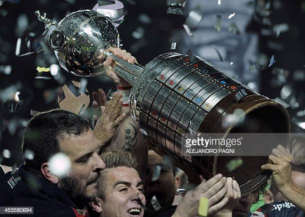Argentina's San Lorenzo players holds up the trophy after winning the Copa Libertadores 2014 final second leg football match against to Paraguay's...