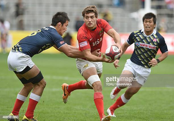 Argentina's Santiago Alvarez tries to dodge a tackle by Japan's Yusaku Kuwazuru during their match at the Tokyo Rugby Sevens in Tokyo on April 4 2015...