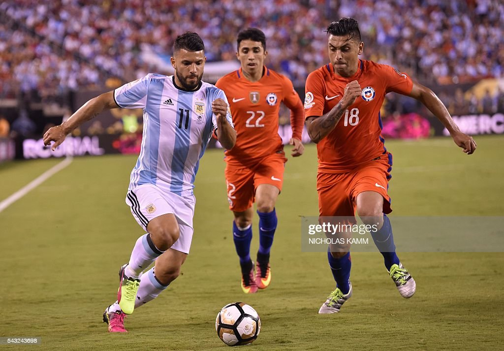 Argentina's Sergio Aguero (L) and Chile's Gonzalo Jara (R) vie for the ball next to Chile's Edson Puch during the Copa America Centenario final in East Rutherford, New Jersey, United States, on June 26, 2016. / AFP / Nicholas KAMM