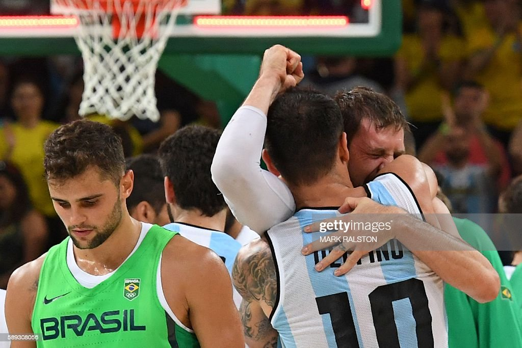TOPSHOT Argentina's shooting guard Carlos Delfino embraces Argentina's small forward Andres Nocioni as Brazil's point guard Raulzinho Neto walks by...