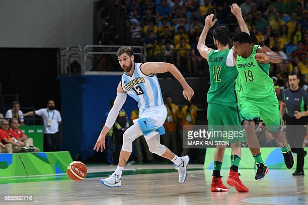 Argentina's small forward Andres Nocioni dribbles away from Brazil's power forward Guilherme Giovannoni and Brazil's shooting guard Leandro Barbosa...