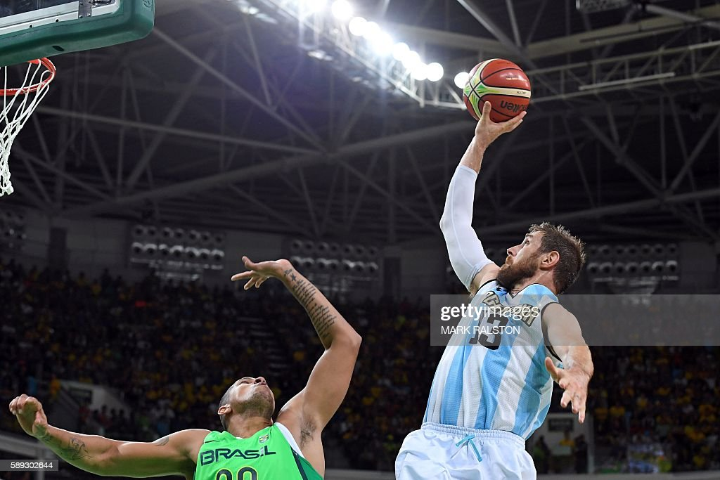 TOPSHOT Argentina's small forward Andres Nocioni takes a shot over Brazil's power forward Rafael Hettsheimeir during a Men's round Group B basketball...