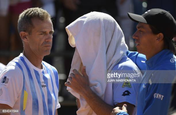 Argentina's team captain Daniel Orsanic gestures while Argentina's tennis player Guido Pella leaves the pitch scorted by teammate Carlos Berlocq...