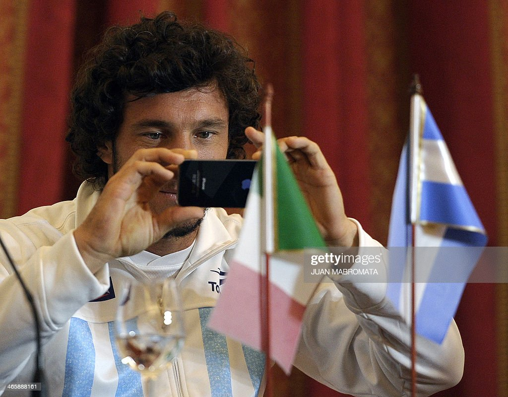 Argentina's tennis player Juan Monaco takes a snapshot with his iPhone during the draw ahead their Davis Cup World Group 1st round matches against Italy in Mar del Plata, Argentina on January 30, 2014.