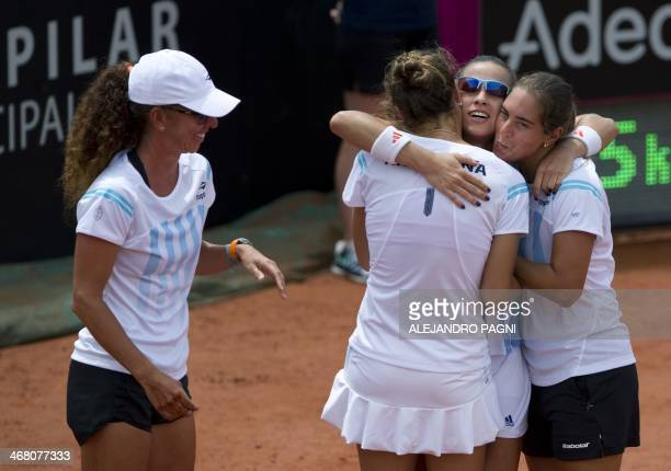 Argentina's tennis player Paula Ormaechea celebrates with her teammates Florencia Molinero Catalina Pella and team captain Maria Jose Gaidano after...
