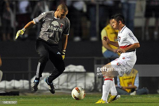 Argentina's Tigre goalkeeper Javier Garcia vies for the ball with Osvaldo of Brazil's Sao Paulo during their 2012 Copa Sudamericana final football...