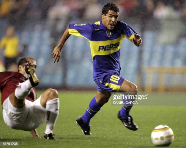 Argentine Carlos Tevez of Boca Juniors and Brazilian Sangaletti of Internacional of Porto Alegre vie for the ball during their semifinal Copa...