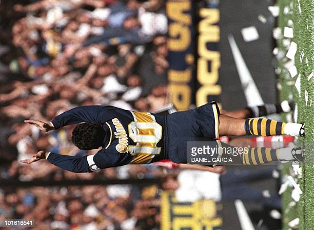 Argentine controversial soccer star Diego Maradona salutes the crowd 14 September before the start of the game in Buenos Aires between his Boca...
