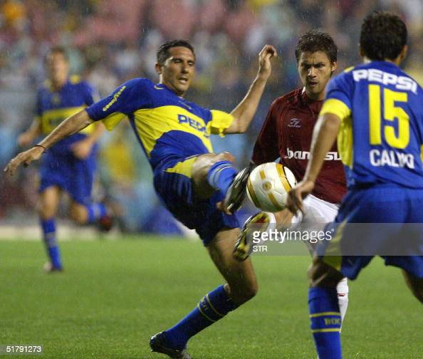 Argentine Diego Cagna and Jose Calvo of Boca Juniors and Elder Granja of Internacional of Porto Alegre vie for the ball during their semifinal Copa...