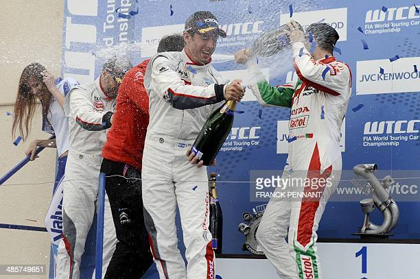 Argentine driver Jose Maria Lopez and Portuguese driver Tiago Montero spray champagne on the podium after the 2nd race of the FIA World Touring Car...
