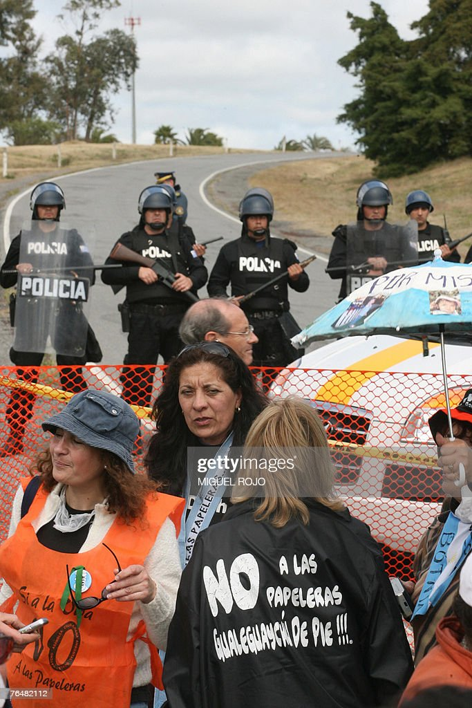 Argentine environmentalists demonstrate as the Uruguayan riot police stands guard in the road leading to the Finnish pulp mill Botnia near Fray Bentos, 305 km northwest of Montevideo, Uruguay, 02 September, 2007. Argentinian environmentalists crossed the border to demostrate against the construction of the pulp mill on the banks of the Uruguay river. AFP PHOTO/Miguel ROJO
