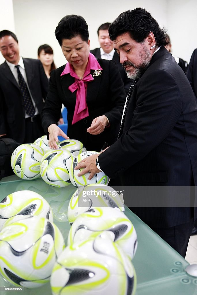 Argentine football great Diego Maradona autographs a set of balls during a meeting with Wei Di, head of the Chinese Football Association, in Beijing on August 16, 2012. Maradona is in Beijing for an eight-day charity tour, while Chinese state media reported that the Argentine football great wants to coach in China, where clubs are spending big bucks to lure international names. CHINA