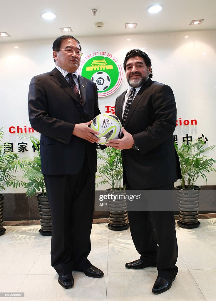 Argentine football great Diego Maradona presents Wei Di (L), head of the Chinese Football Association, with an autographed ball during a meeting in Beijing on August 16, 2012. Maradona is in Beijing for an eight-day charity tour, while Chinese state media reported that the Argentine football great wants to coach in China, where clubs are spending big bucks to lure international names. CHINA