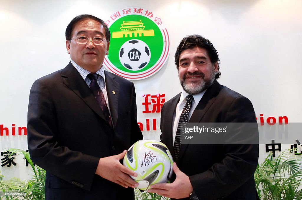 Argentine football great Diego Maradona presents Wei Di, head of the Chinese Football Association, with an autographed ball during a meeting in Beijing on August 16, 2012. Maradona is in Beijing for an eight-day charity tour, while Chinese state media reported that the Argentine football great wants to coach in China, where clubs are spending big bucks to lure international names. CHINA