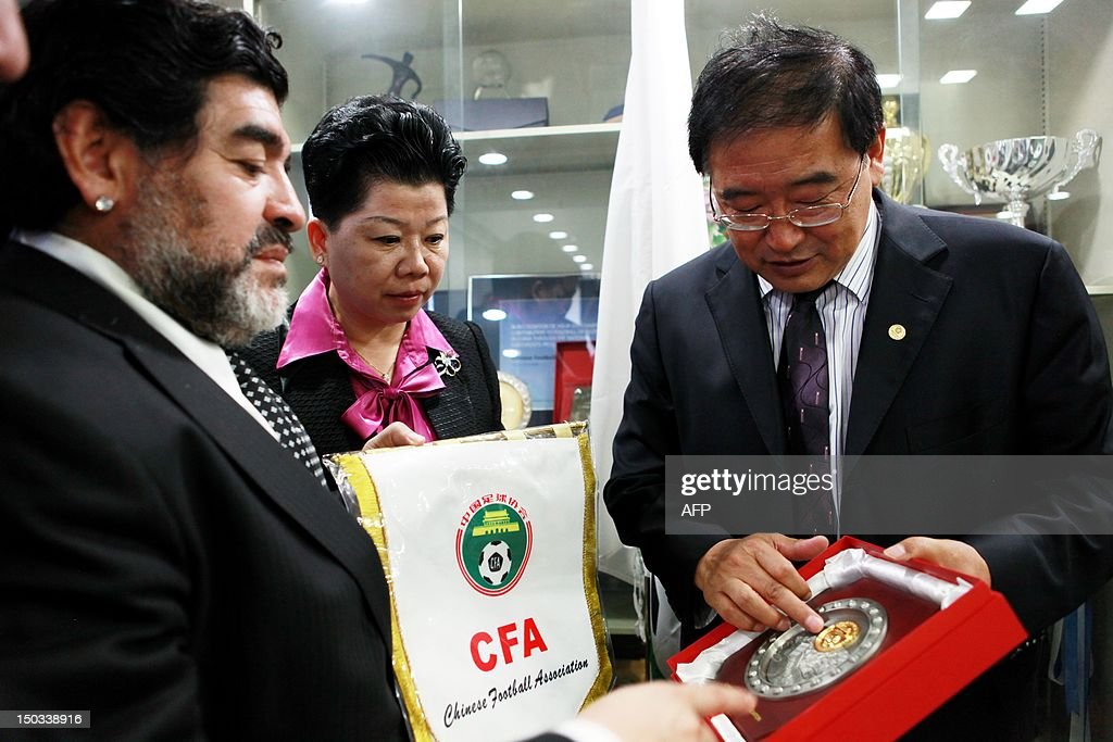 Argentine football great Diego Maradona receives a souvenir from Wei Di (R), head of the Chinese Football Association, in Beijing on August 16, 2012. Maradona is in Beijing for an eight-day charity tour, while Chinese state media reported that the Argentine football great wants to coach in China, where clubs are spending big bucks to lure international names. CHINA OUT AFP PHOTO