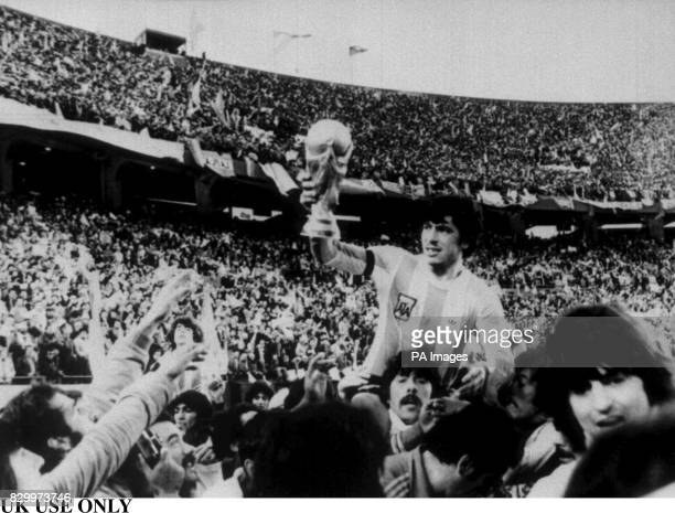 Argentine football team captain Daniel Passarella is carried on the shoulders of fans as he proudly shows off the FIFA World Cup trophy his team won...