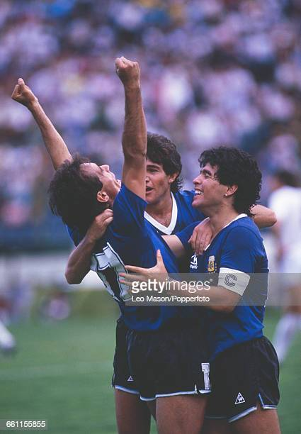 Argentine footballer Diego Maradona celebrates with goalscorer Pedro Pasculli after Argentina went ahead 10 against Uruguay in the first round of the...
