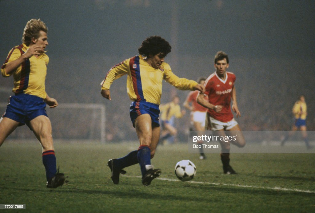 Argentine footballer Diego Maradona on the ball during the European Cup Winner's Cup quarter final, second leg, against Manchester United at Old Trafford, Mancester, 21st March 1984. On the right is United midfielder, Bryan Robson. United won the match 3-0 and the quarter final won 3–2 on aggregate.