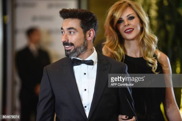 Argentine footballer Ezequiel Lavezzi and his wife pose on a red carpet upon arrival to attend Argentine football star Lionel Messi and Antonella...