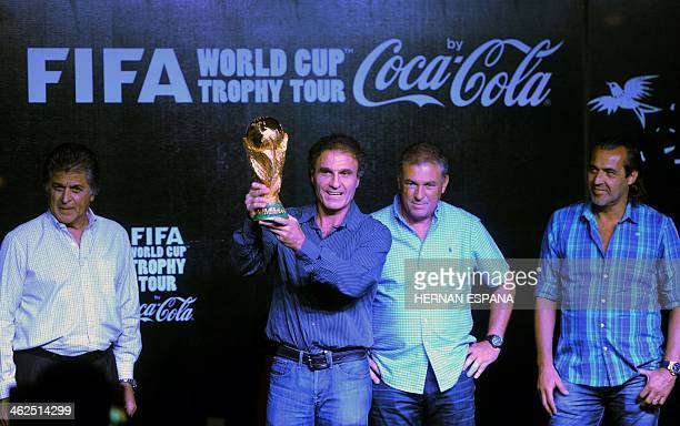 Argentine former football player Oscar Ruggeri holds up the FIFA World Cup next to Argentine former football players Ubaldo Matildo Fillol Julio...