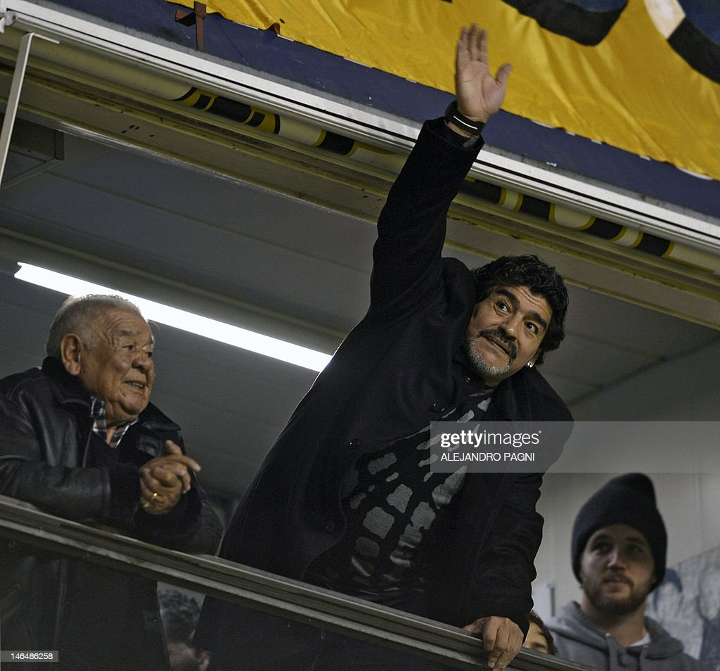 Argentine former footballer and United Arab Emirates Al Wasl team coach Diego Maradona (C) waves next his father 'Don Diego' before the start of the match between Boca Juniors and Arsenal at 'La Bombonera' stadium in Buenos Aires, Argentina, on June 17, 2012. AFP PHOTO / Alejandro PAGNI