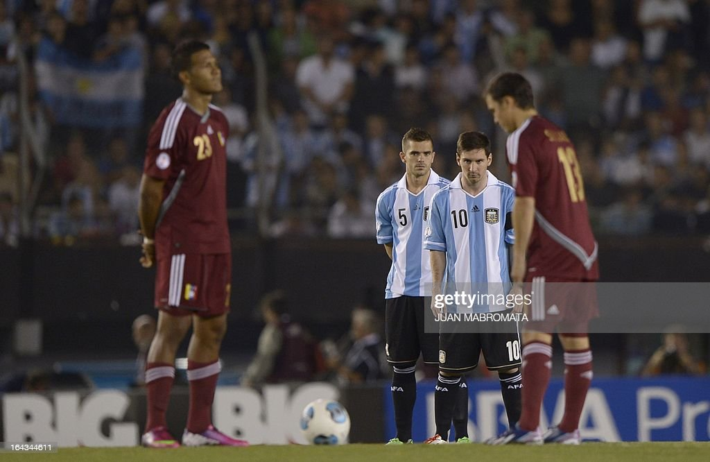 Argentine midfielder Fernando Gago and forward Lionel Messi are seen during a moment of silence for the late President Hugo Chavez before their FIFA World Cup Brazil 2014 South American qualifying football match against Venezuela in Buenos Aires, Argentina on March 22, 2013.