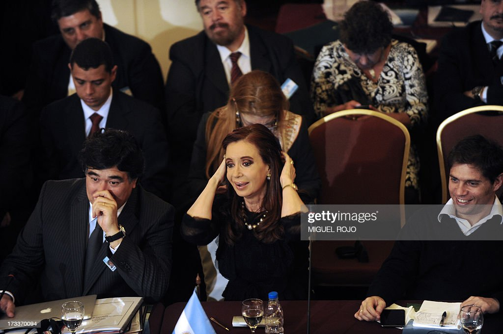 Argentine President Cristina Fernandez de Kirchner (C) gestures as she sits next to the Legal and Technical Secretary of Argentina's Presidency, Carlos Alberto Zannini (L) and Deputy Economy Minister Axel Kicillof, during the plenary session of the XLV Mercosur Summit, at the headquarters of the bloc in Montevideo on July 12, 2013. Leaders of the South American trade bloc that includes Argentina, Brazil, Uruguay and Venezuela, agreed to a statement reaffirming the fundamental right of asylum, Maduro said Friday amid a test of wills with Washington over the fate of US intelligence leaker Edward Snowden.