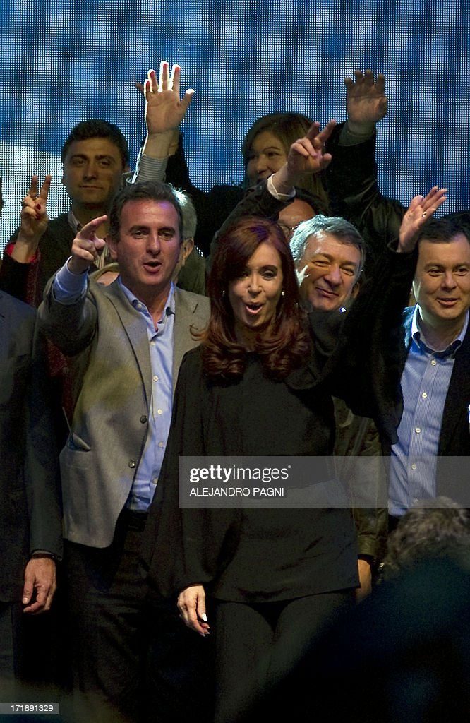 Argentine President Cristina Fernandez de Kirchner (R) waves at the end of her speech during the presentation of the ruling Frente para la Victoria (FPV) party candidates for the Congress, in Buenos Aires on June 29, 2013. Argentina will hold primary --obligatory-- elections next August 11. AFP PHOTO / Alejandro PAGNI