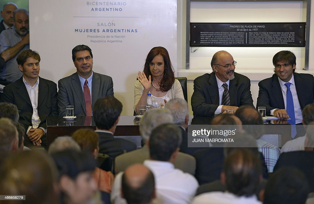 Argentine President Cristina Fernandez de Kirchner (C) waves next to Argentinian Economy Minister Axel Kicillof (L), Argentinian Chief of Cabinet Jorge Capitanich (2-L), Argentinian Work Minister Carlos Tomada and ANSES (National Administration of Social Security) Director Diego Bossio (R) at the Government Palace in Buenos Aires on February 4, 2014. Kirchner announced a rise in basic pensions. AFP PHOTO / Juan Mabromata