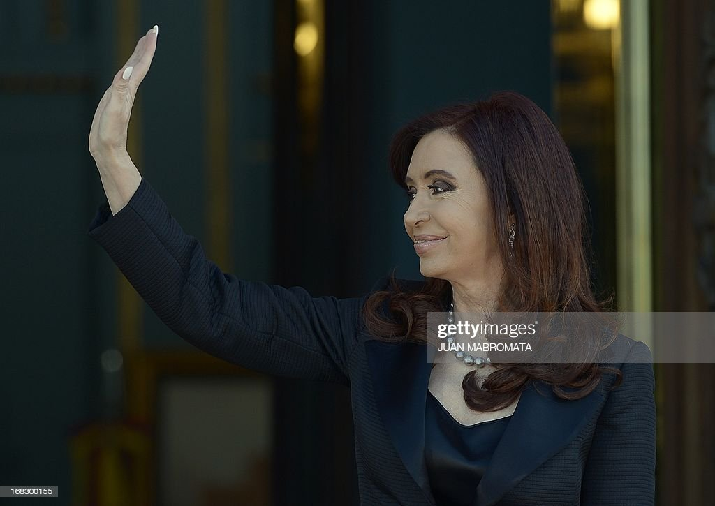 Argentine President Cristina Fernandez de Kirchner waves to people from the Government palace as she waits the arrival of Venezuelan President Nicolas Maduro in Buenos Aires on May 8, 2013. Maduro arrived today from Uruguay and afterwards will travel to Brazil. AFP PHOTO / Juan Mabromata