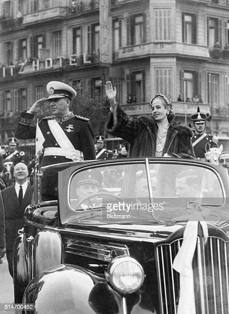 Argentine President Juan Peron salutes and his wife Eva waves during a procession through the streets of Buenos Aires after Peron took the oath of...
