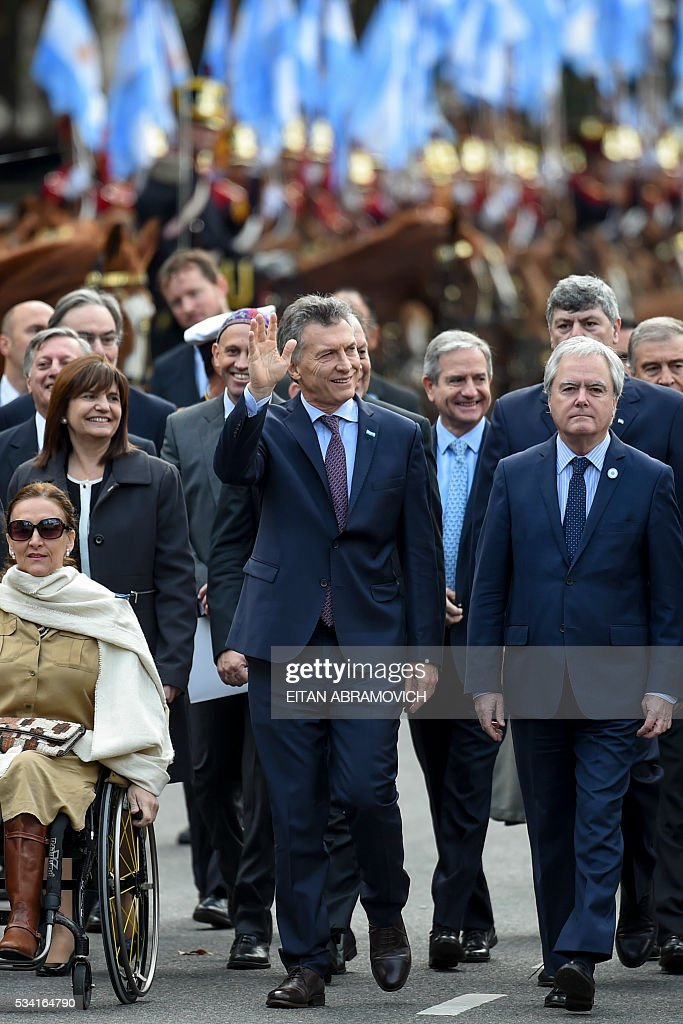 Argentine President Mauricio Macri waves as he walks to the Cathedral to attend the Te Deum to commemorate the 206th anniversary of the May Revolution, in Buenos Aires, on May 25, 2016. / AFP / EITAN