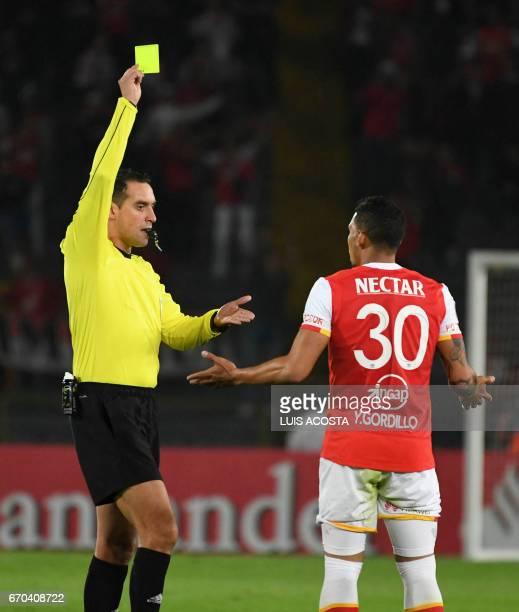 Argentine referee Fernando Rapallini shows the yellow card to Colombia's Santa Fe footballer Yeison Stiven Gordillo during the Copa Libertadores 2017...