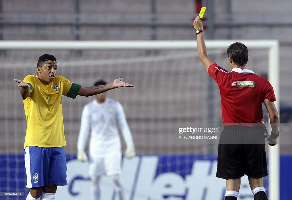 Argentine referee Patricio Loustau (R) shows a yellow card to Brazilian defender Wallace during their South American U-20 Championship Group B football match against Uruguay, at Bicentenario stadium in San Juan, Argentina, on January 12, 2013. Four South American teams will qualify for the FIFA U-20 World Cup Turkey 2013. Uruguay won 3-2.