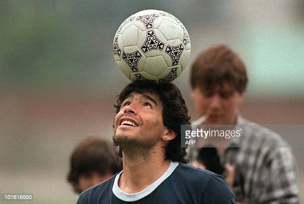 Argentine soccer star Diego Maradona wearing a diamond earring balances a soccer ball on his head as he walks off the practice field following the...
