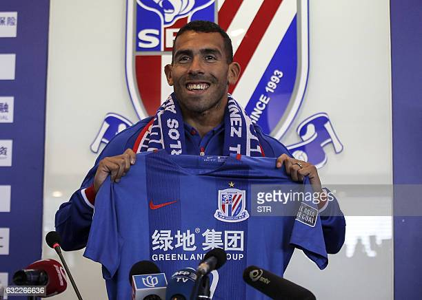 Argentine striker Carlos Tevez poses with a jersey of his new club Shanghai Shenhua during a press conference in Shanghai on January 21 2017 Tevez...