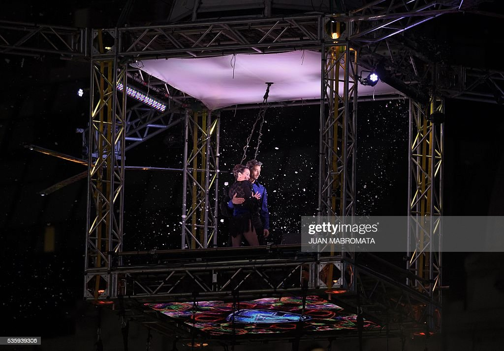 Argentine tango dancer Mora Godoy poses with her partner after performing in a hanging platform next to the Obelisk to mark a new Guinness record of tango dancing at heights during the opening of the TV program 'Show Match' in Buenos Aires on May 30, 2016. / AFP / JUAN