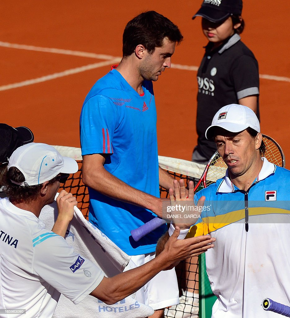 Argentine tennis player Carlos Berlocq (R) and team captain Martin Jaite (L) greet as French Gilles Simon walks to the bench during the 2013 Davis Cup World Group quarterfinal single tennis match at Parque Roca stadium in Buenos Aires on April 7, 2013. Argentina won by 3-2 and will play in semifinals with the Czech Republic.