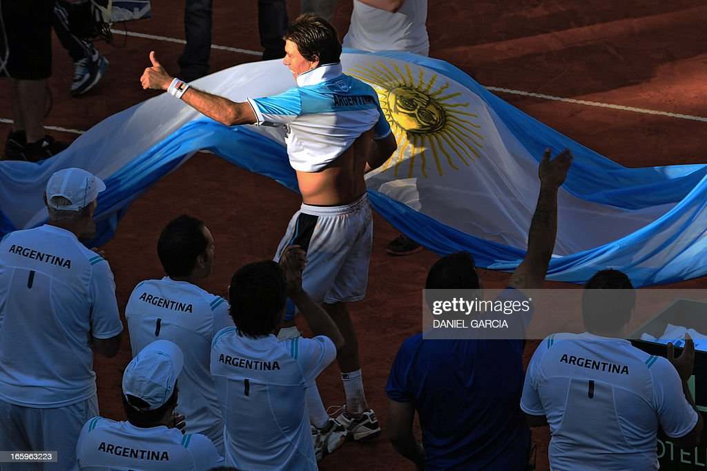 Argentine tennis player Carlos Berlocq carries an Argentine national flag as he celebrates after defeating French Gilles Simon by 6-4, 5-7, 6-4, 6-4 during their 2013 Davis Cup World Group quarterfinal single tennis match at Parque Roca stadium in Buenos Aires on April 7, 2013. Argentina won by 3-2 and will play in semifinals with the Czech Republic.