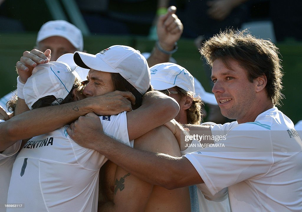 Argentine tennis player Carlos Berlocq (C) celebrates with teammates after defeating French tennis player Gilles Simon (out of frame) by 6-4, 5-7, 6-4, 6-4 in their 2013 Davis Cup World Group quarterfinal single tennis match at Parque Roca stadium in Buenos Aires on April 7, 2013. Argentina won the series by 3-2 and qualified for semifinals. AFP PHOTO / JUAN MABROMATA