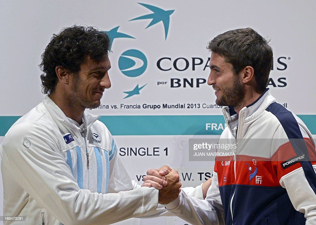 Argentine tennis player Juan Monaco (L) and France's Gilles Simon shake hands during the draw ahead of their 2013 Davis Cup World Group quarterfinals single match in Buenos Aires on April 4, 2013.