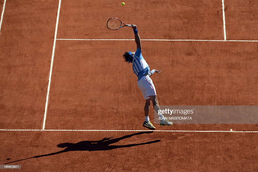 Argentine tennis player Juan Monaco serves the ball to French tennis player Jo-Wilfried Tsonga during the Davis Cup quarterfinals tennis match at Mary Teran de Weiss stadium in Roca Park in Buenos Aires on April 7, 2013.