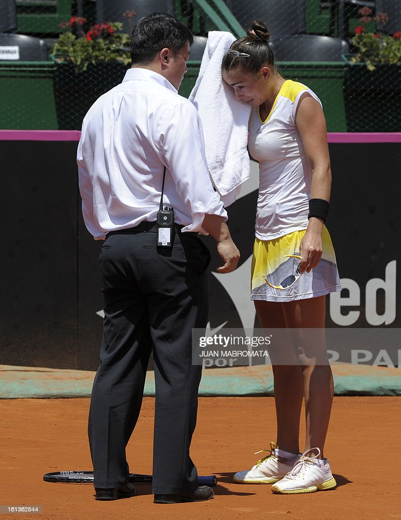 Argentine tennis player Paula Ormaechea (R) gestures next to referee Tony Cho before retiring from the 2013 Fed Cup World Group II first round single tennis match against Swedish Sofia Arvidsson, at Parque Roca stadium in Buenos Aires on February 10, 2013. Arvidsson won 7-5, 6-7, 3-2 (ret). AFP PHOTO / Juan Mabromata