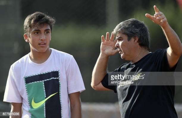 Argentine tennis player Roman Burruchaga son of former footballer Jorge Burruchaga listens to his coach Marcelo Miguez during a training session in...