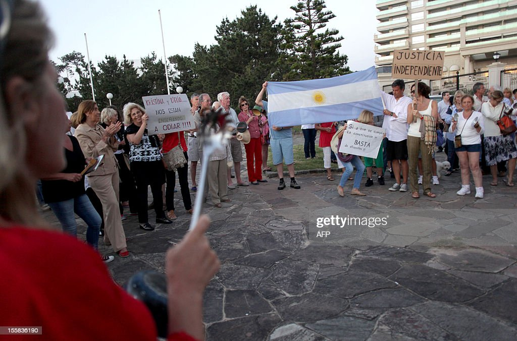 Argentines bang cooking pots during a 'cacerolazo' to protest against the possible reelection of President Cristina Fernandez de Kirchner and the growing insecurity, corruption and restrictions on the purchasing of US dollars, in the Uruguayan seaside resort of Punta del Este, 135 km east of Montevideo, on November 8, 2012. Thousands of opponents of Fernandez de Kirchner gathered in the Argentine capital Buenos Aires and other cities across the world banging their cooking pots in a noisy protest against any possible bid she might run for a third term. 'Say no to reelection,' said the call to protest which was sent across the country via social media websites. Fernandez, 59, is currently barred by the Argentine Constitution from running for a third consecutive term, but her supporters in the Congress have been lobbying for a constitutional amendment.
