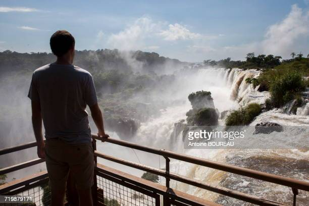 Argentinia, Man seen from behind looking at the Iguazus falls on the Argentinian side